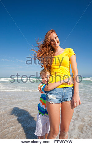 Portrait of son, with arms around smiling mother, on sunny beach - Stock Photo