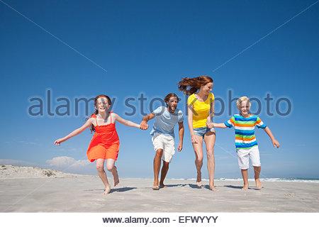 Happy family running toward camera, holding hands, on sunny beach - Stock Photo