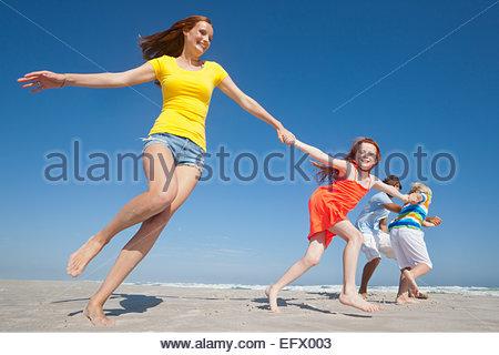 Happy family, holding hands, running on sunny beach - Stock Photo