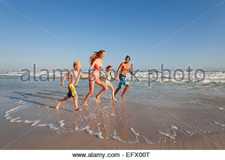 Happy family running through water, whilst holding hands, along sunny beach - Stock Photo