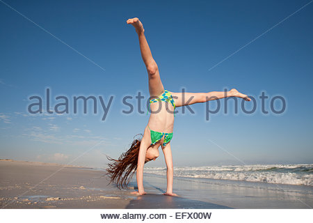 Redheaded Girl doing handstand on sunny beach - Stock Photo