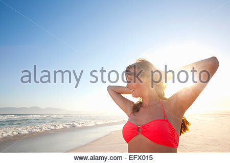 Smiling woman, with arms raised behind head, on sunny beach - Stock Photo