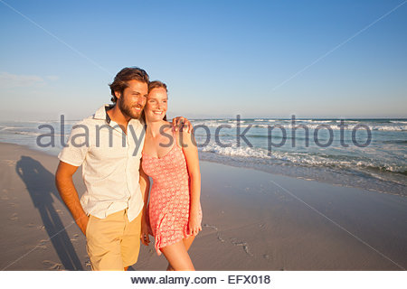 Smiling couple, man with arm round woman, walking along sunny beach - Stock Photo
