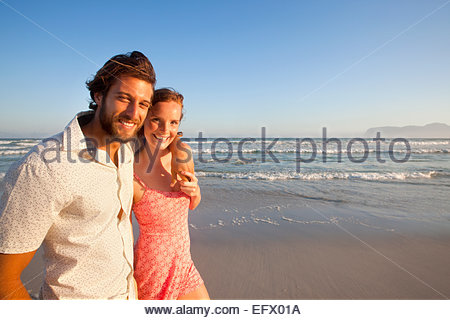 Smiling couple looking at camera, man with arm round woman, walking along sunny beach - Stock Photo