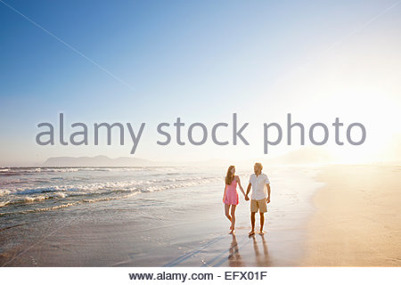 Couple, holding hands, walking along sunny beach - Stock Photo