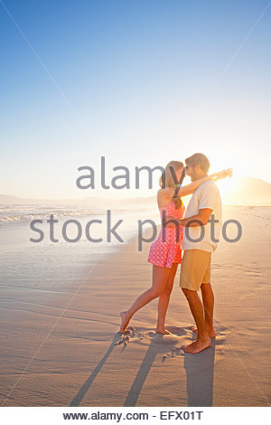 Romantic couple embracing, looking into each others eyes, on sunny beach - Stock Photo