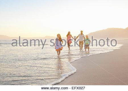 Happy family holding hands on sunny beach - Stock Photo