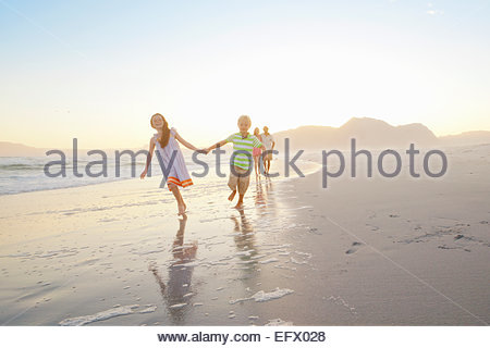 Happy family, with son and daughter holding hands, walking on sunny beach - Stock Photo