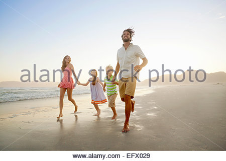 Happy family, holding hands, running on sunny beach - Stock Photo