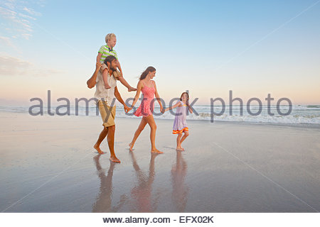 Happy family walking, holding hands and son having piggy-back, on sunny beach - Stock Photo