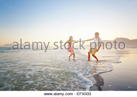 Couple, holding hands, playfully walking through waves on sunny beach - Stock Photo