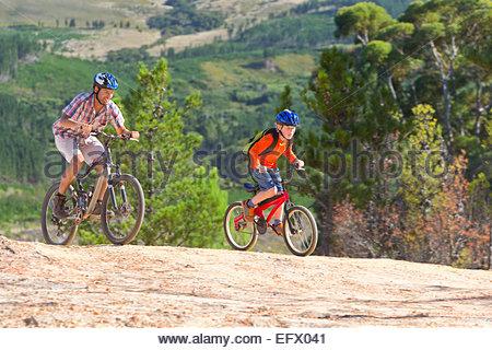 Father and son mountain biking, on mountain path - Stock Photo