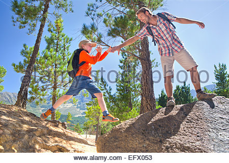 Father helping son climb, on mountain path - Stock Photo