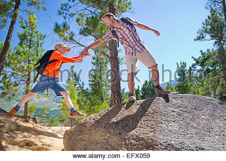 Father helping son climb on mountain path - Stock Photo