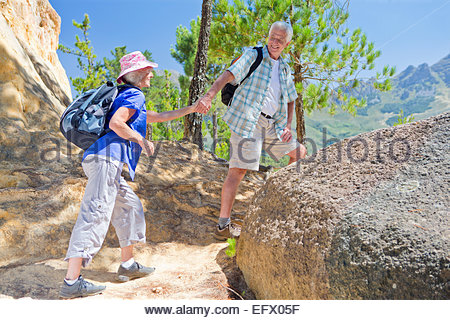Senior couple hiking on mountain path - Stock Photo