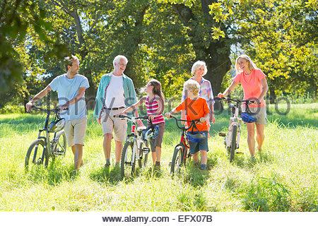 Multi generation family, pushing mountain bikes, in treelined field - Stock Photo