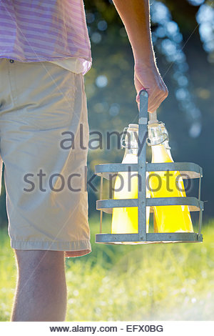 Close up of man carrying crate with bottles of juice - Stock Photo
