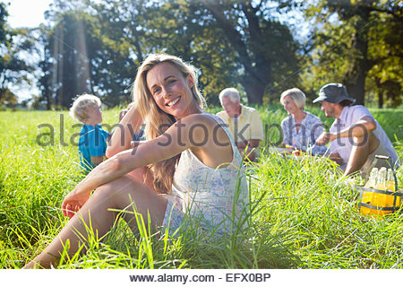 Portrait of smiling woman and multi generation having picnic in treelined field - Stock Photo