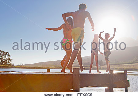 Happy family running and jumping on jetty - Stock Photo