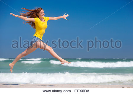 Happy woman leaping in air on sunny beach - Stock Photo