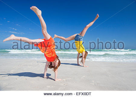 Mother and daughter cart wheeling on sunny beach - Stock Photo