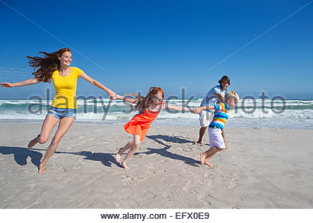 Happy family holding hands, running and pulling each other along sunny beach - Stock Photo