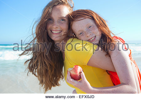 Portrait of smiling girl holding apple, embracing mother, on sunny beach - Stock Photo