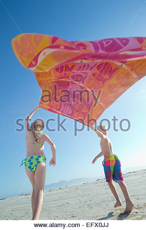 Young boy and girl holding towel above head in the wind on sunny beach - Stock Photo