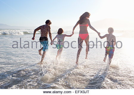 Happy family in swimwear running through waves, holding hands, on sunny beach - Stock Photo