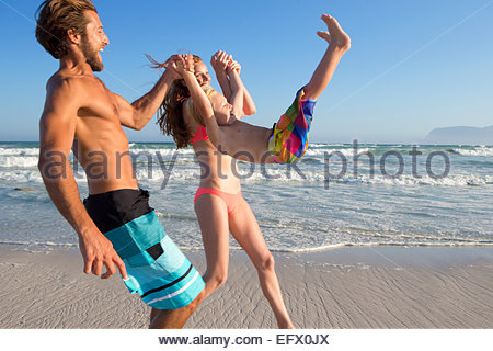 Happy couple swinging son in the air on sunny beach - Stock Photo