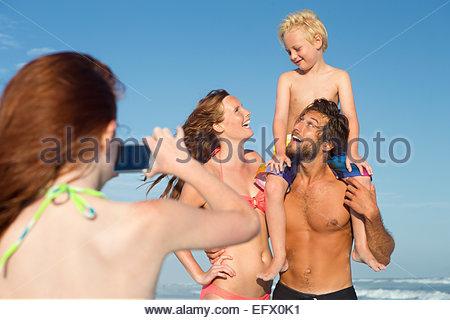 Girl taking photo of family on sunny beach - Stock Photo