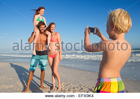 Boy taking photo of mother, father and sister on sunny beach - Stock Photo