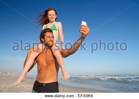 Father, with daughter sitting on shoulders, taking selfie on sunny beach - Stock Photo