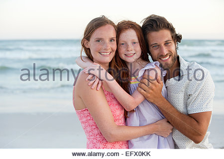 Portrait of family, smiling at camera, embracing on sunny beach - Stock Photo