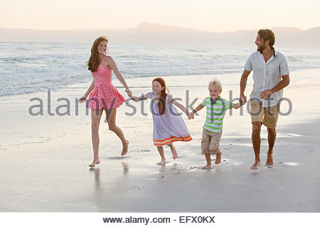 Happy family holding hands, running along sunny beach - Stock Photo