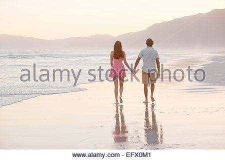 Couple walking into distance, holding hands, on sunny beach - Stock Photo