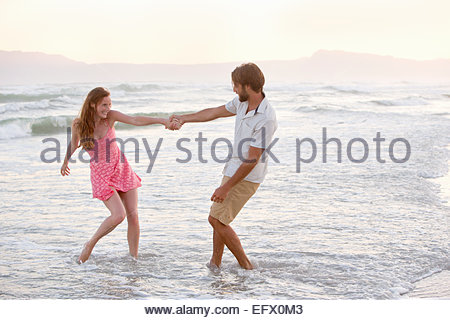 Couple, playfully pulling each other into the sea on sunny beach - Stock Photo