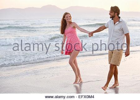 Couple, holding hands, walking on sunny beach - Stock Photo