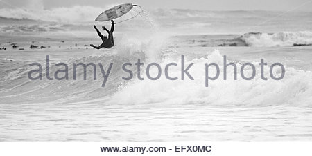 Surfer falling off surfboard on wave - Stock Photo