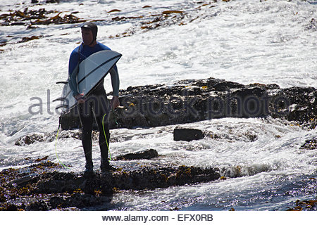 Man with surfboard standing on rocks - Stock Photo