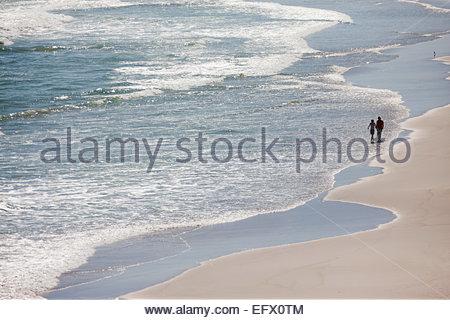 Couple walking through waves on beach - Stock Photo