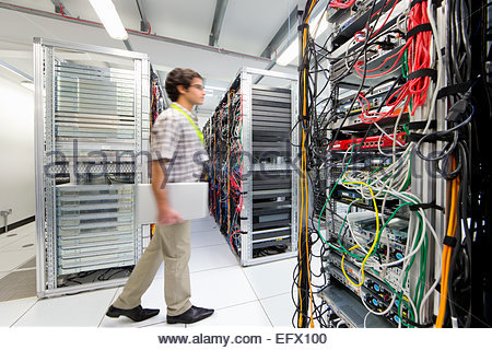 Technician walking through server room of data center - Stock Photo