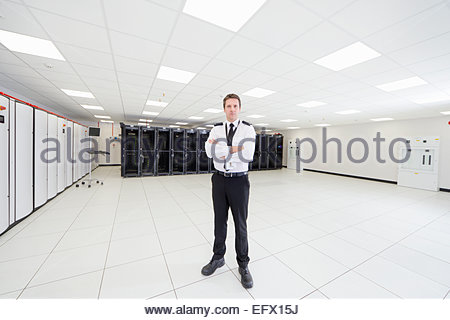 Security guard standing with arms crossed in server room - Stock Photo