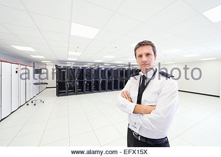 Security guard standing with arms crossed, looking at camera, in server room - Stock Photo