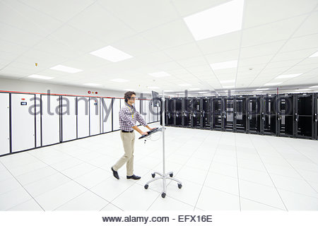 Technician walking through server room with portable computer - Stock Photo