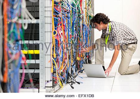 Technician, kneeling, working on laptop computer in Server room of data center - Stock Photo