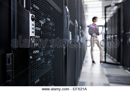 Technician with laptop, checking aisle of server storage cabinets ...