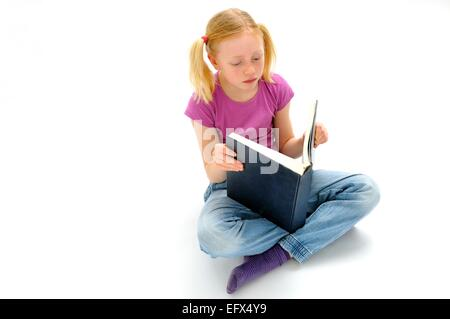 Pre teen girl reading a large book - Stock Photo