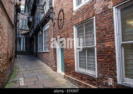An old sign for a cordwainer (shoemaker) is high up on a wall, down the narrow alley of Lady Peckett's Yard, York, - Stock Photo