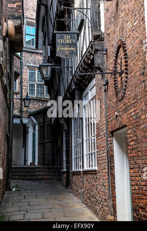 An old sign for a cordwainer (shoemaker) is high up on a wall in a narrow alley or ginell. Lady Peckett's Yard, - Stock Photo